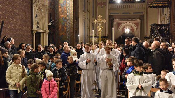 Прихожане и священнослужители на Рождественской мессе в Латинском кафедральном соборе (Митрополичья базилика Успения Пресвятой Девы Марии) во время празднования католического Рождества во Львове