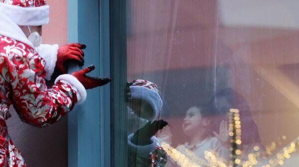 Сотрудник департамента по делам гражданской обороны, чрезвычайным ситуациям и пожарной безопасности города Москвы в костюме Деда Мороза поздравляет пациентов Морозовской детской больницы