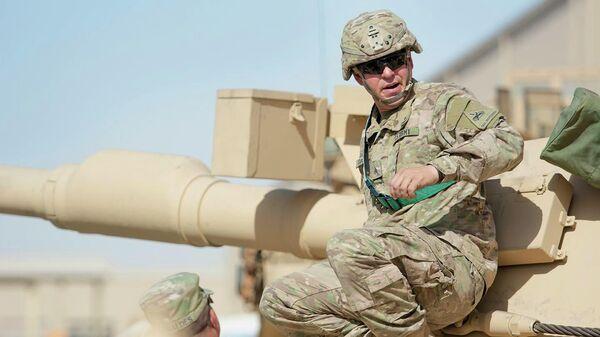 Сержант-механик армии США Д осматривает танк Абрамс M1A2 во время учений  в лагере Арифжан, Кувейт