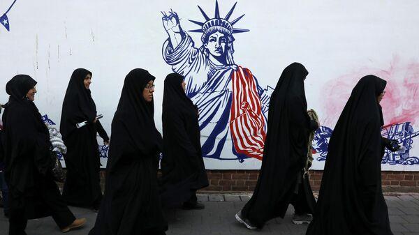 Женщины в траурных одеждах у граффити с изображением статуи Свободы в Тегеране, Иран