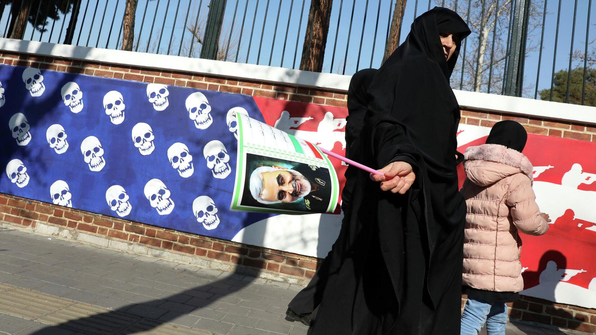 Женщина возвращается с похорон генерала Касема Сулеймани мимо посольства США в Тегеране  - РИА Новости, 1920, 30.12.2020