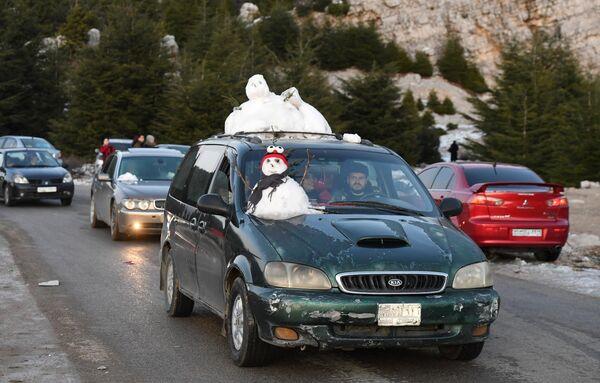 Сирийцы привозят на машинах снег с гор на побережье в горной части Латакии