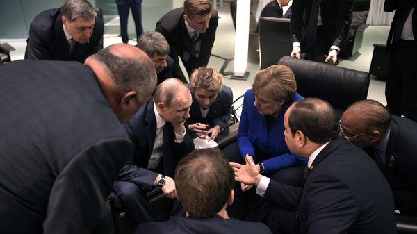 Президент РФ Владимир Путин и федеральный канцлер ФРГ Ангела Меркель во время встречи на полях Международной конференции по Ливии в Берлине