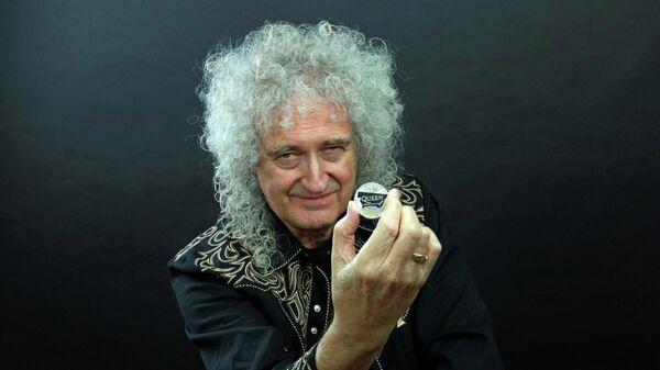 Гитарист группы Queen Брайан Мэй позирует с 5-фунтовой монетой,  выпущенной с логотипом группы