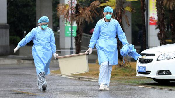 Медицинские работники у здания больницы в городе Ухань, провинция Хубэй