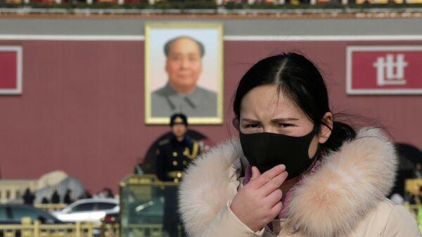 Девушка в маске на площади Тяньаньмэнь в Пекине