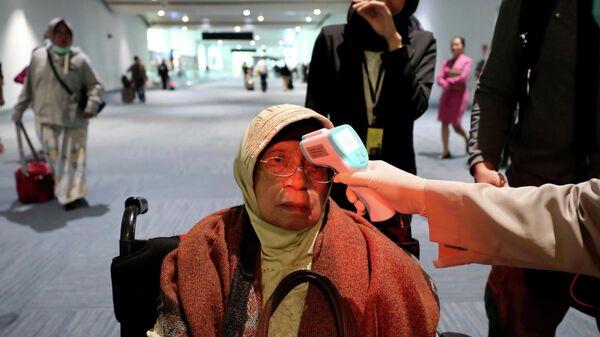 Медицинский работник проверяет температуру тела пассажирки в Индонезии