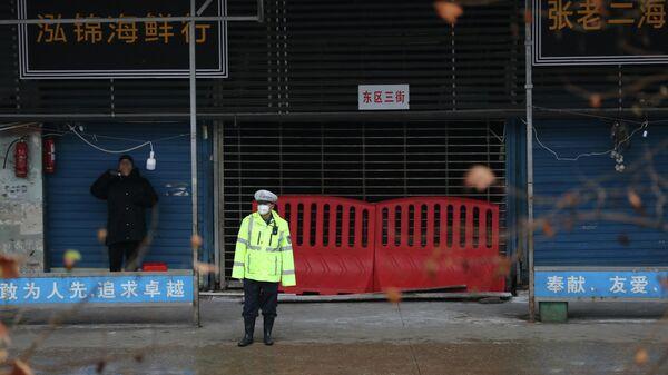 Сотрудник полиции у закрытого рынка морепродуктов в Ухане, КНР