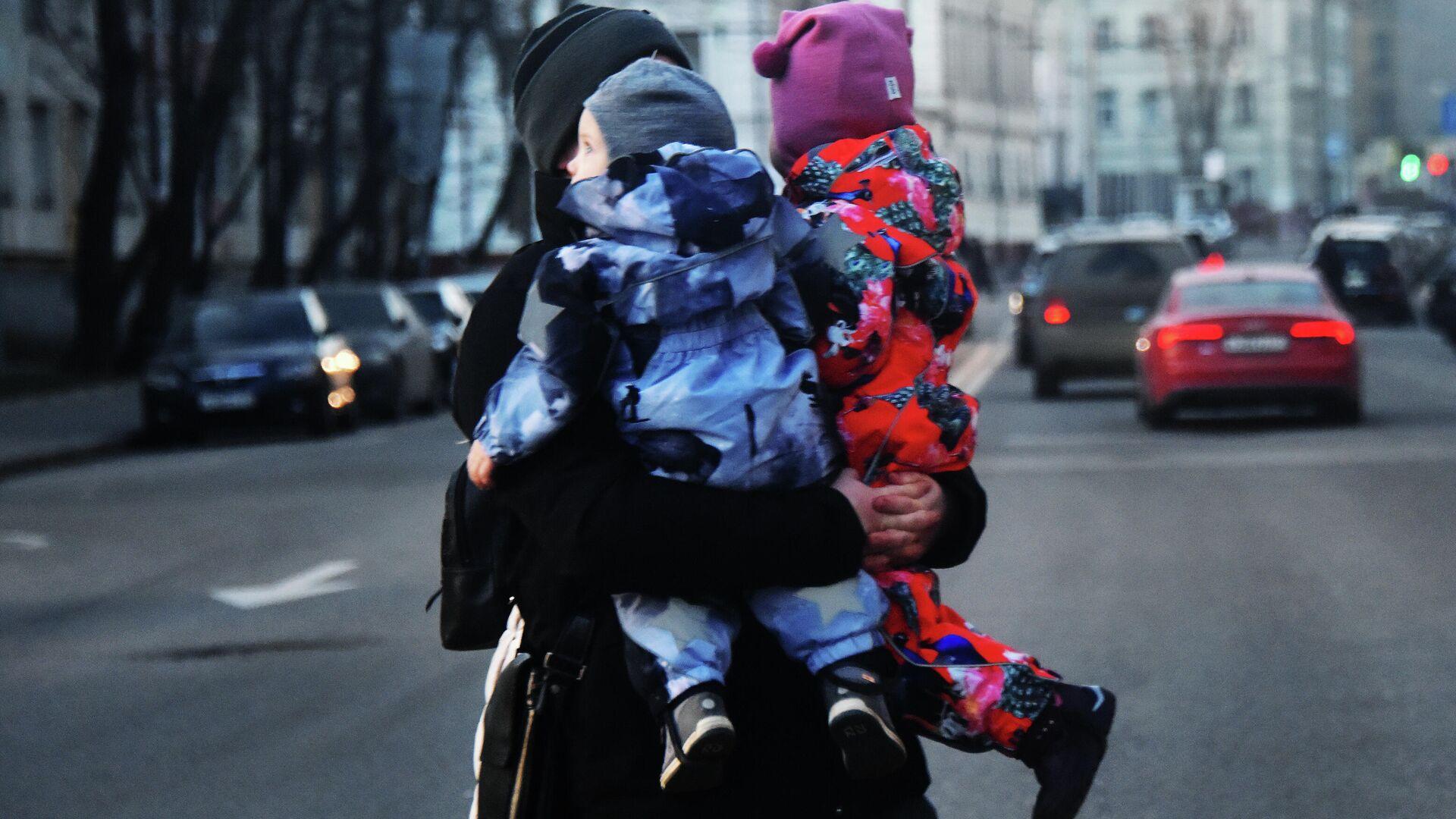Женщина с двумя детьми на руках переходит дорогу - РИА Новости, 1920, 20.02.2020