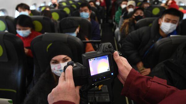 Сотрудник Роспотребназдора обследует при помощи тепловизора пассажиров рейса авиакомпании S7, прибывшего из Пекина, в аэропорту Толмачево