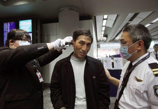 Сотрудники аэропорта Гонконга проверяют пассажиров, прибывших из Мексики
