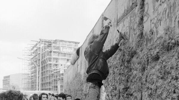 Житель Берлина отбивает кусок бетона от Берлинской стены