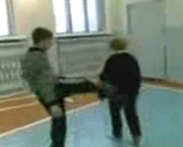 Кадр из видео, на котором запечатлено, как несколько подростков избивают в спортзале пожилую учительницу физкультуры