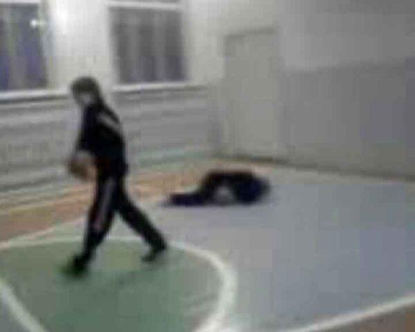Кадр из видео, на котором запечатлено, как подростки избивают в спортзале пожилую учительницу физкультуры