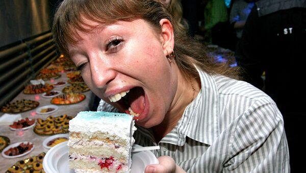 Девушка ест кусок 84-хкилограммового торта на празднике, посвященном Международному дню студента.