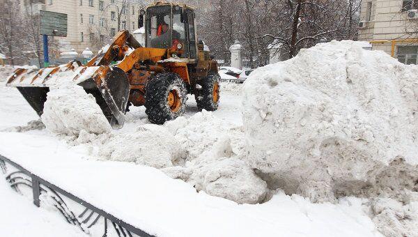 Трактор убирает снег во дворе одного из домов