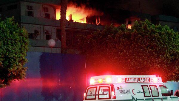 Скорая помощь около горящего здания службы безопасности в Триполи после авиаудара коалиции 17 мая