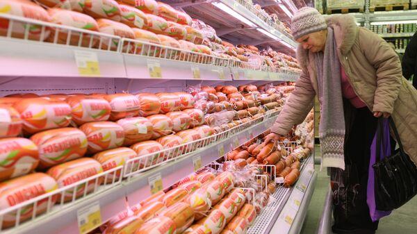 Покупательница у прилавка с колбасой в гипермаркете Лента.