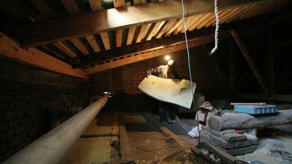 Рабочий утепляет чердак многоэтажного дома. Архив