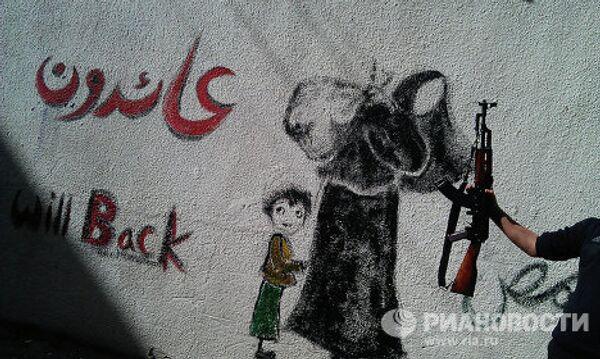 Графити с изображением беженцев и надписью на арабском и английком языках-  вернемся