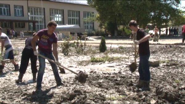 Волонтеры расчищают улицы от ила после наводнения в Новомихайловском