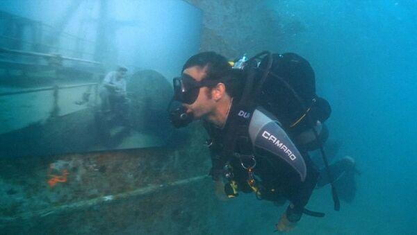 Аквалангисты рассматривают фотоснимки в галерее на затонувшем корабле