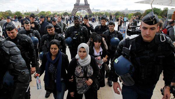 Французские жандармы проверяют документы у мусульманок недалеко от Эйфелевой Башни