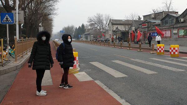 Женщины в медицинских масках переходят улицу в Пекине