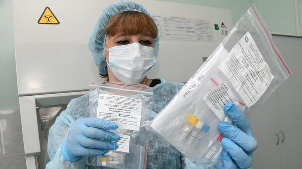 Сотрудница Центра гигиены и эпидемиологии в Забайкальском крае держит набор реагентов для выявления РНК коронавируса 2019-nCoV
