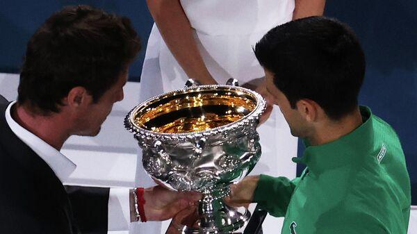Бывшая первая ракетка мира россиянин Марат Сафин вручает сербу Новаку Джоковичу трофей за победу на Открытом чемпионате Австралии по теннису