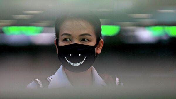 Сотрудница аэропорта Суварнабхуми в защитной маске в Бангкоке
