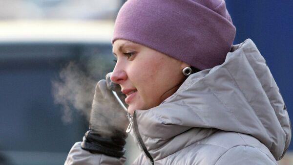 Девушка говорит по телефону в мороз на остановке автобуса в Новосибирске
