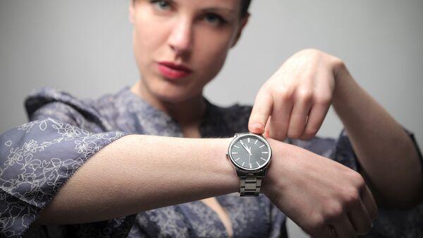 Девушка указывает на время