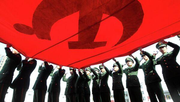 Военизированные полицейские держат флаг Коммунистической партии Китая