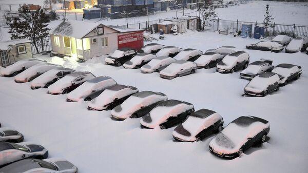 Занесенная снегом стоянка машин на улице Профсоюзная в Москве