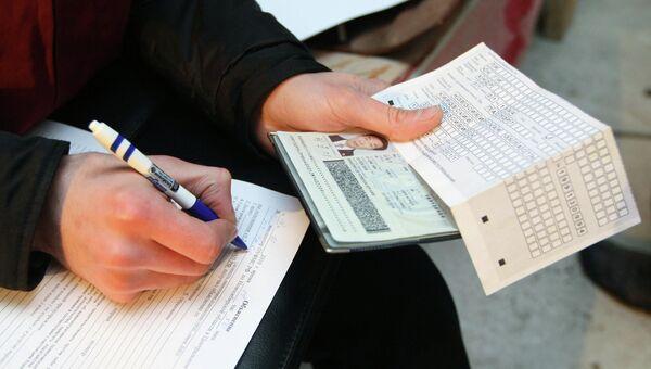 Сотрудник федеральной миграционной службы  проводит проверку документов у иностранных рабочих
