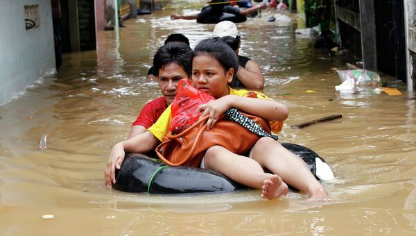 Жители Джакарты передвигаются по затопленной улице