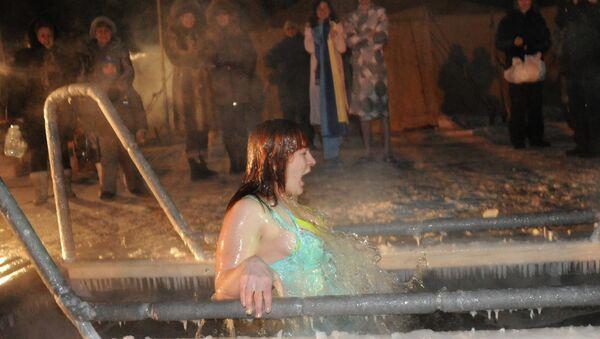Женщина купается в проруби в праздник Крещения Господня