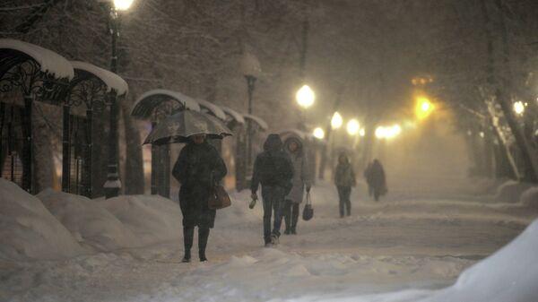 Прохожие на Гоголевском бульваре во время сильного снегопада в Москве