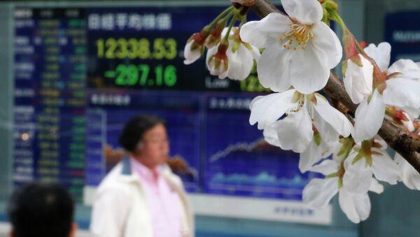 Цветущая сакура на фоне фондовой биржи в Токио