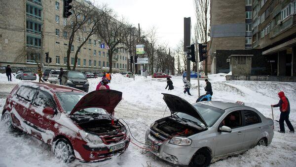 Автомобили на одной из улиц Киева после сильного снегопада