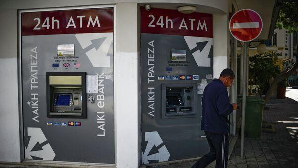 Мужчина проходит мимо банкоматов Cyprus Popular Bank (CPB). Архив