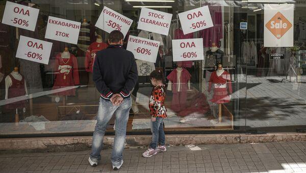 Люди смотрят на объявления о скидках в магазине города Никосии