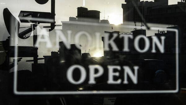 Табличка с надписью Открыто на двери одного из банков Кипра