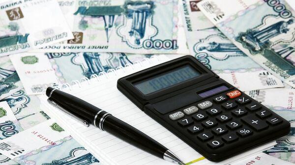 Блокнот и калькулятор на фоне российских рублей