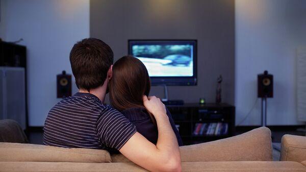 Девушка и молодой человек смотрят телевизор