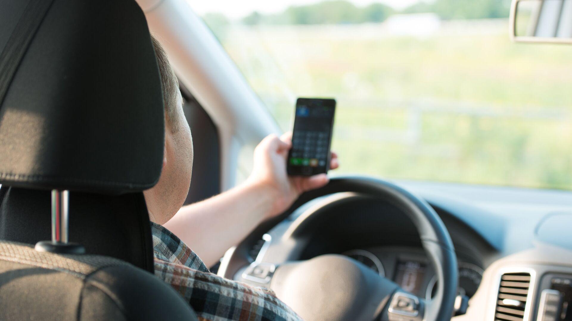 Молодой человек пользуется мобильным телефоном за рулем автомобиля - РИА Новости, 1920, 12.08.2021