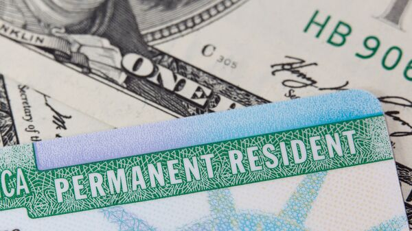 Грин-карта и доллары США. Архивное фото