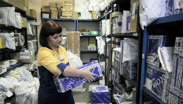 Сотрудница красноярского почтового отделения ищет посылку в отделе приемки посылок. Архив