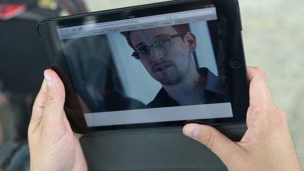 Журналист изучает фото бывшего сотрудника ЦРУ Эдварда Сноудена
